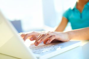Close-up shot of a female learner typing on the laptop keyboard